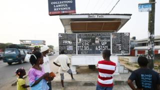 """People looking at the """"Daily Talk"""" chalkboard paper in Monrovia, Liberia - Sunday 31 December 2017"""