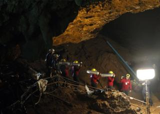 Thai officials carry oxygen tanks through a cave complex during a rescue operation for a missing football team at the Tham Luang cave in Tham Luang Khun Nam Nang Noon Forest Park in Chiang Rai province, Thailand, 30 June 2018