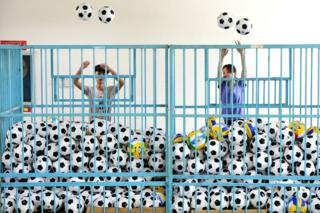 Employees sort footballs at a company manufacturing sports equipment, in Yiwu, Zhejiang province, China, 5 July 2018