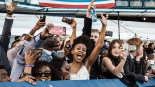 People cheer during the main race of the 2018 edition of the Vodacom Durban July horse race in Durban, on 7 July 2018.